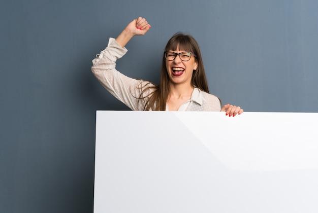 Frau mit gläsern über der blauen wand, die ein plakat für hält, fügen ein konzept ein Premium Fotos