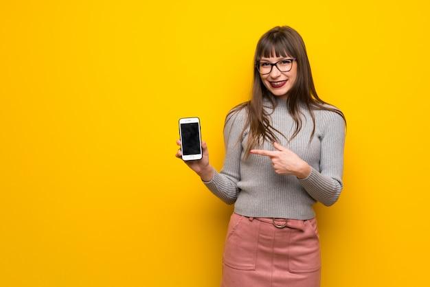 Frau mit gläsern über der gelben wand, die das mobile glücklich und gezeigt worden sein würden Premium Fotos
