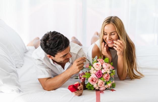 Frau mit glücklicher lächelnder reaktion nach dem liebhaber, der um bittet, heiraten mit ring auf bett Premium Fotos