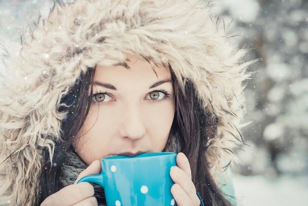 Frau mit großem blauem becher des heißen getränks während des kalten tages. Premium Fotos