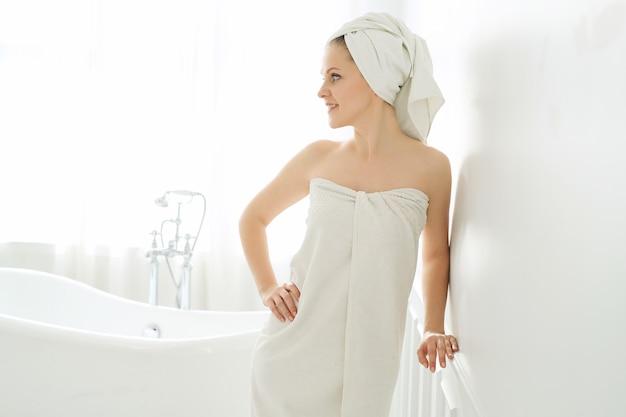 Frau mit handtuch auf kopf und körper nach dem duschen Kostenlose Fotos