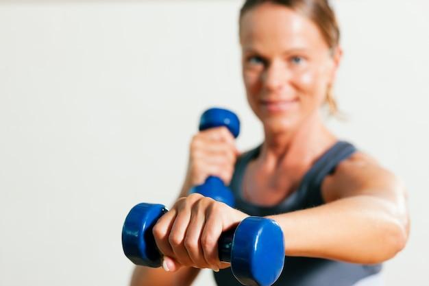 Frau mit hanteln im fitnessstudio Premium Fotos