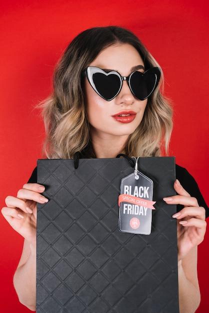 Frau mit herzsonnenbrille und schwarzer freitag-tasche Kostenlose Fotos