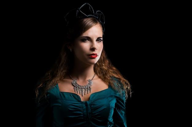 Frau mit hexenkostüm und einer schwarzen krone Premium Fotos