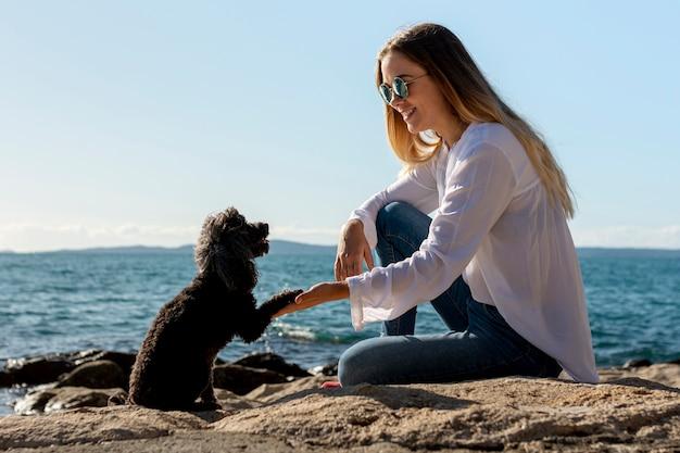 Frau mit hund am meer Kostenlose Fotos