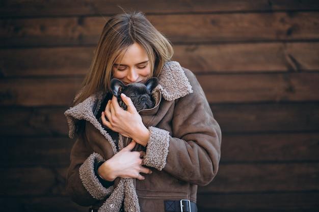 Frau mit ihrer französischen bulldogge des haustieres auf hölzernem hintergrund Kostenlose Fotos