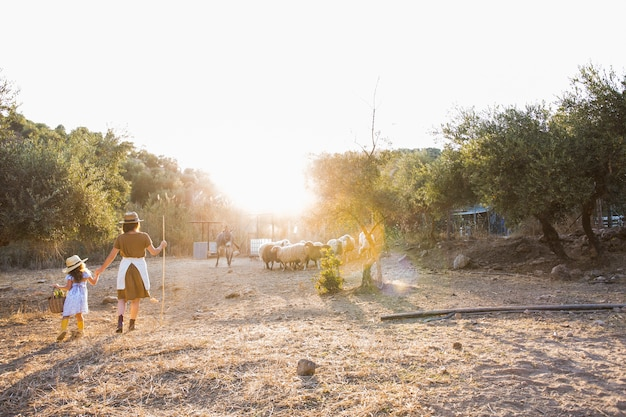 Frau mit ihrer tochter, die auf dem gebiet mit tieren geht Kostenlose Fotos