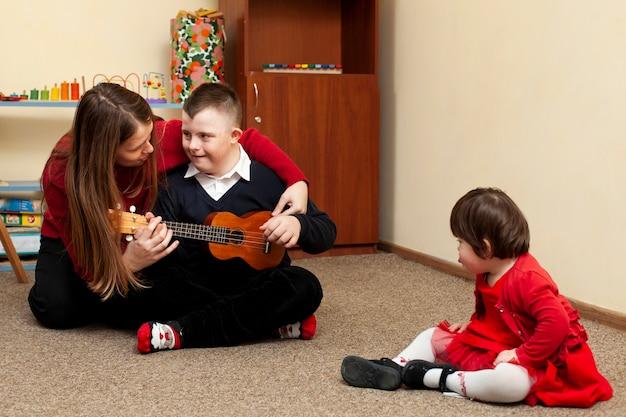Frau mit jungen mit down-syndrom und gitarre Premium Fotos