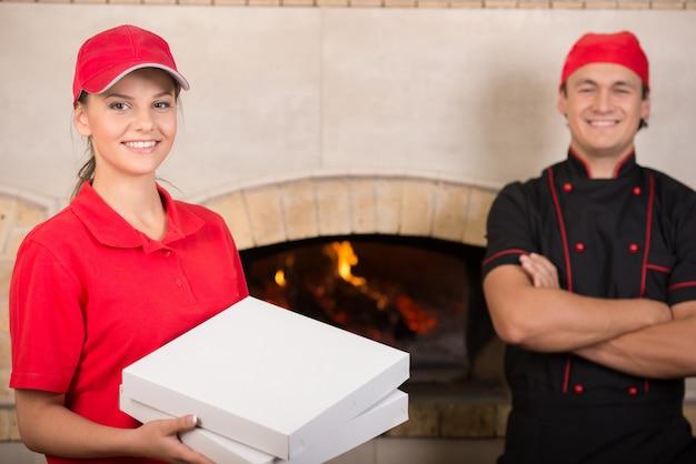 Frau mit kästen pizza in der roten uniform und im chef im schwarzen. Premium Fotos