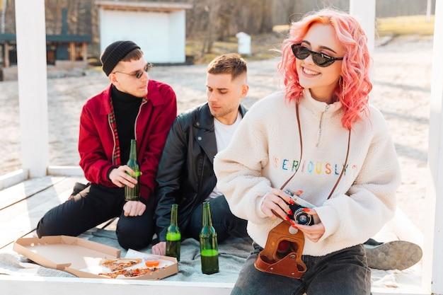 Frau mit kamera und paar mann auf picknick Kostenlose Fotos