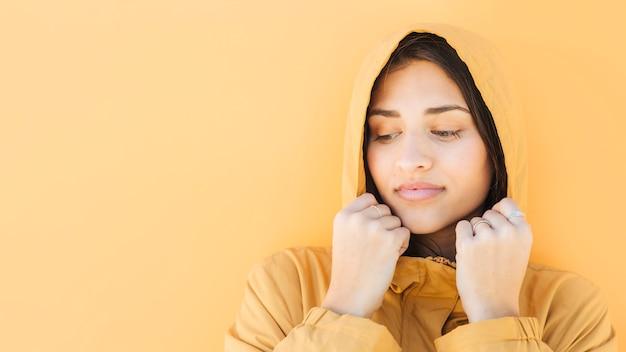 Frau mit kapuzenjacke steht gegen gelbe oberfläche Kostenlose Fotos
