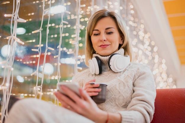 Frau mit kopfhörern um den hals nahe weihnachtslichtern Kostenlose Fotos