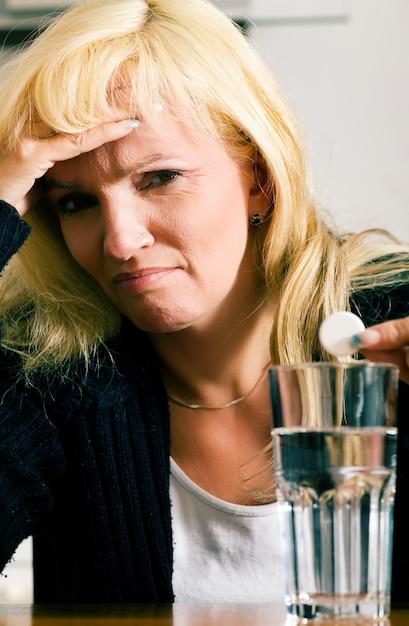 Frau mit kopfschmerzen im begriff, eine pille zu haben Premium Fotos