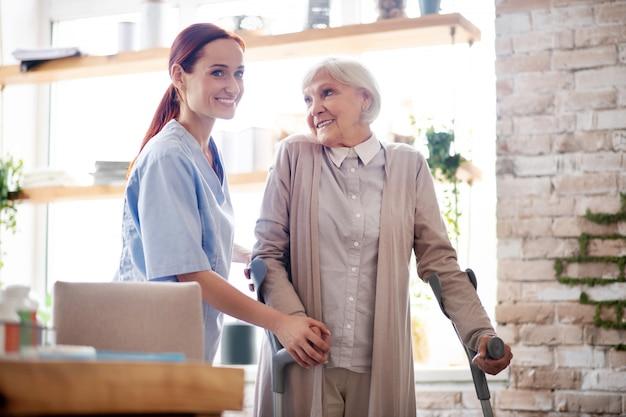 Frau mit krücken lächelnd, während sie mit der pflegekraft spricht Premium Fotos