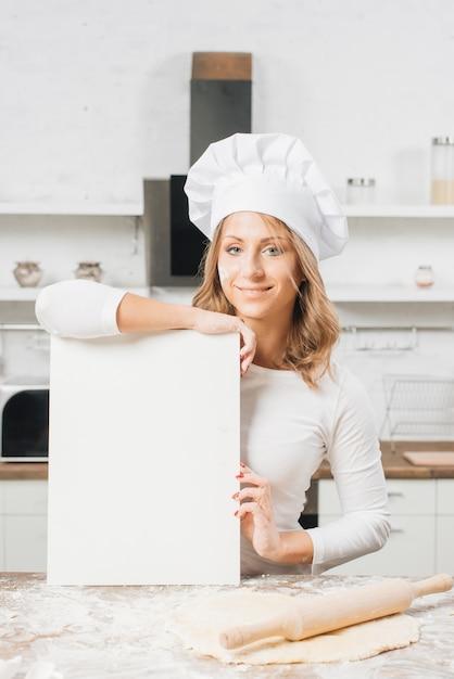 Frau mit leerem papier in der küche Kostenlose Fotos