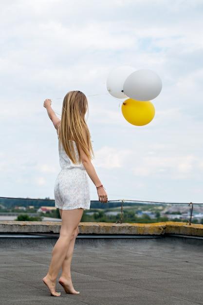 Frau mit luftballons auf dem dach des hauses Premium Fotos