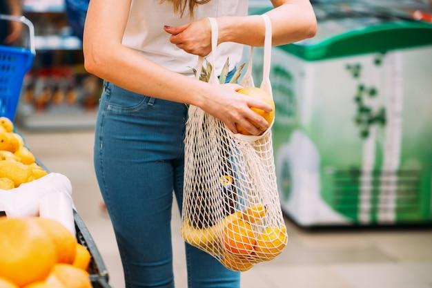 Frau mit maschentasche voll vom frischgemüse, das im geschäft, nullabfallkonzept, eco freundlich kauft Premium Fotos