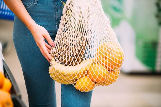 Frau mit maschentasche voll vom frischgemüse, das im geschäft, nullabfallkonzept kauft Premium Fotos