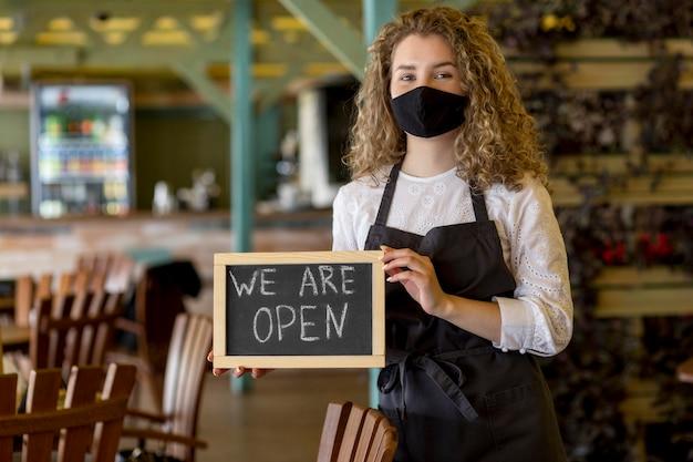 Frau mit maske, die tafel mit offenem zeichen hält Kostenlose Fotos