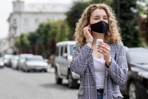 Frau mit maske im freien mit airpods Kostenlose Fotos