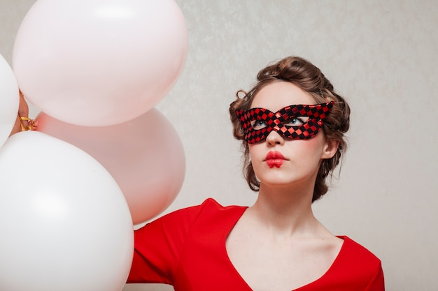 Frau mit maske und rotem kleid mit ballonen Kostenlose Fotos