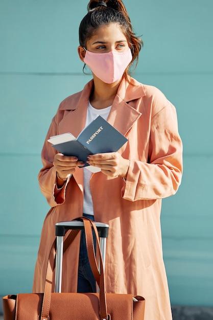 Frau mit medizinischer maske am flughafen und pass während der pandemie Kostenlose Fotos