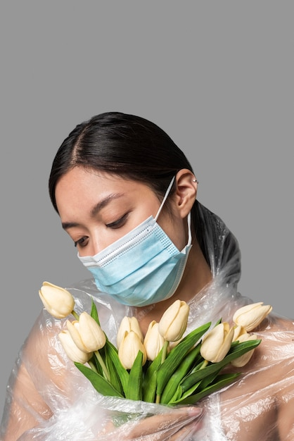 Frau mit medizinischer maske, die ihren körper mit plastik