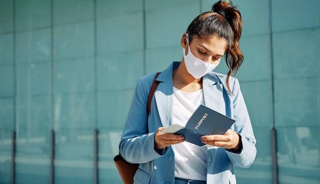 Frau mit medizinischer maske, die ihren pass am flughafen während der pandemie überprüft Kostenlose Fotos