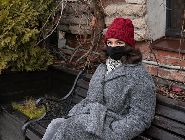 Frau mit medizinischer maske draußen auf bank Kostenlose Fotos