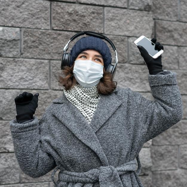 Frau mit medizinischer maske in der stadt, die musik mit kopfhörern und smartphone hört Kostenlose Fotos