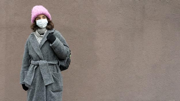 Frau mit medizinischer maske in der stadt und kopieren raum Kostenlose Fotos