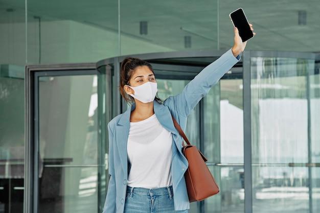 Frau mit medizinischer maske und smartphone, die ein taxi am flughafen während der pandemie hageln Kostenlose Fotos