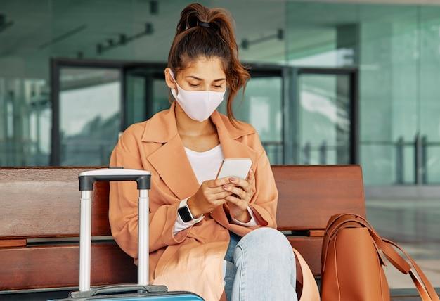 Frau mit medizinischer maske unter verwendung des smartphones am flughafen während der pandemie Kostenlose Fotos