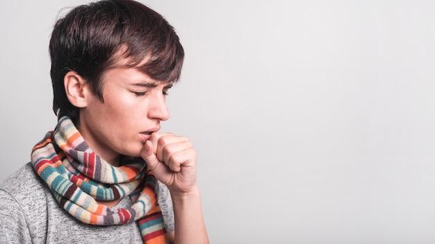 Frau mit mehrfarbigem schal um ihren hals, der gegen grauen hintergrund hustet Kostenlose Fotos