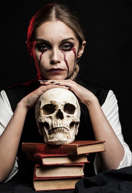 Frau mit menschlichem schädel und büchern Kostenlose Fotos
