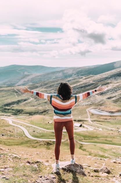 Frau mit offenen armen gegen himmel und gebirgstal. Premium Fotos