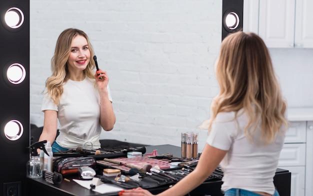 Frau mit pinsel für make-up stehen am spiegel Kostenlose Fotos