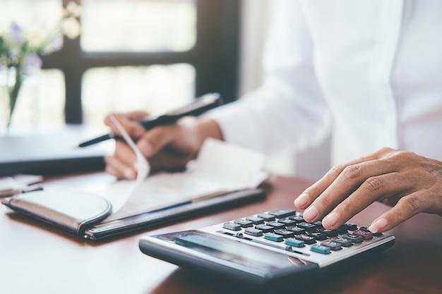 Frau mit rechnungen und taschenrechner. frau, die taschenrechner verwendet, um rechnungen am tisch im büro zu berechnen. Premium Fotos
