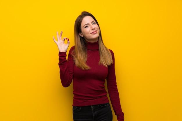 Frau mit rollkragen über der gelben wand, die okayzeichen mit den fingern zeigt Premium Fotos