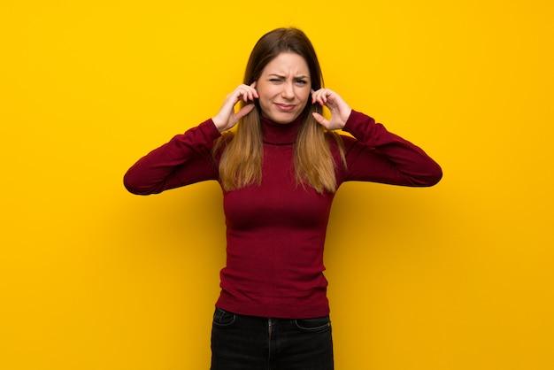 Frau mit rollkragen über gelber wand frustriert und ohren bedeckt Premium Fotos