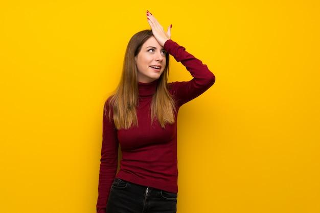 Frau mit rollkragenpullover über gelber wand hat etwas realisiert und beabsichtigt die lösung Premium Fotos