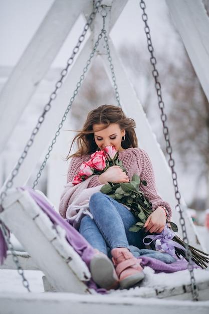 Frau mit rosen draußen im winter, der auf schwingen sitzt
