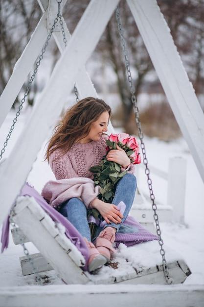 Frau mit rosen draußen im winter, der auf schwingen sitzt Kostenlose Fotos