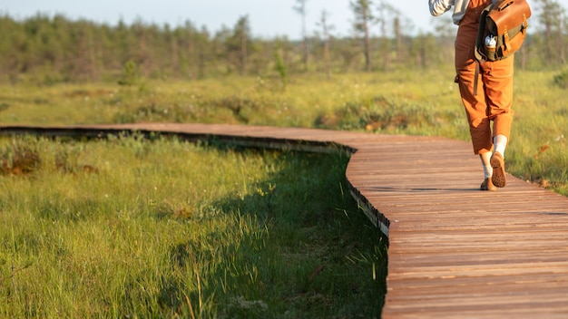Frau mit rucksack auf ökologischem wanderweg im sommer, abgeschnittener schuss. naturforscher, der wildtier- und ökotourismus-abenteuer auf dem weg erkundet Premium Fotos