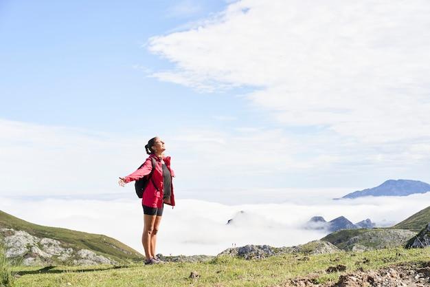 Frau mit rucksack stehend und mit offenen armen oben auf einem berg und irgendwo schauend. er trägt eine rote jacke. im hintergrund sieht man berge, die von nebel umgeben sind. Premium Fotos