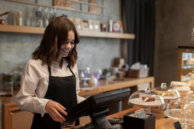 Frau mit schutzblech an der registrierkasse in der kaffeestube Kostenlose Fotos