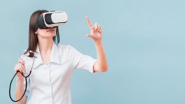 Frau mit stethoskop unter verwendung des virtual-reality-headsets Kostenlose Fotos