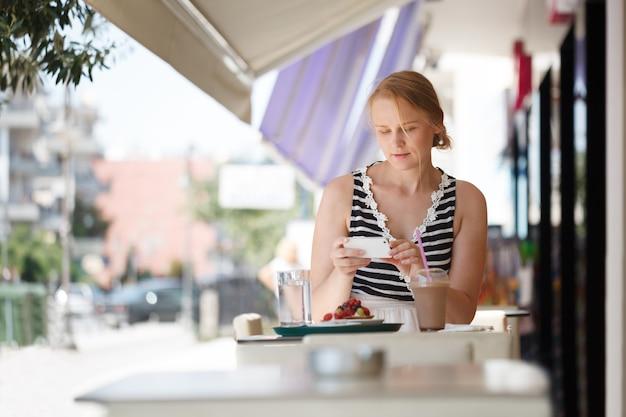 Frau mit telefon café im im freien Premium Fotos