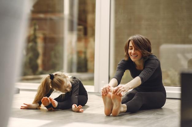 Frau mit tochter ist in der gymnastik beschäftigt Kostenlose Fotos