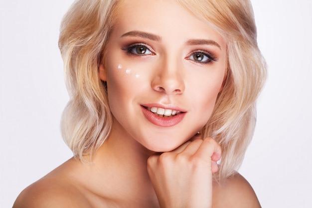 Frau mit tropfen der kosmetischen creme unter auge Premium Fotos